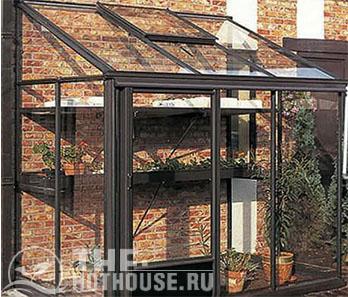 На фото пристенная теплица, установленная вплотную к кирпичному дому